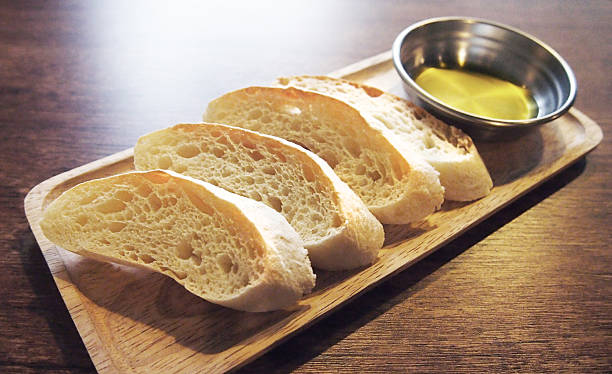 scheiben ciabatta-brot mit olive öl auf holz platte - tablett holz stock-fotos und bilder