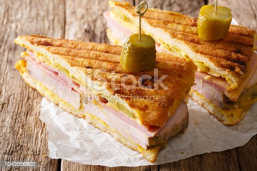 Sliced Cuban sandwich close-up on paper on a table. horizontal, rustic