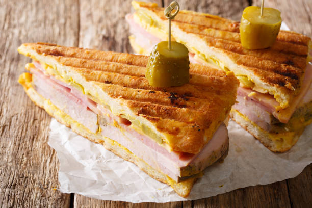 Sliced Cuban sandwich close-up on paper on a table. horizontal stock photo