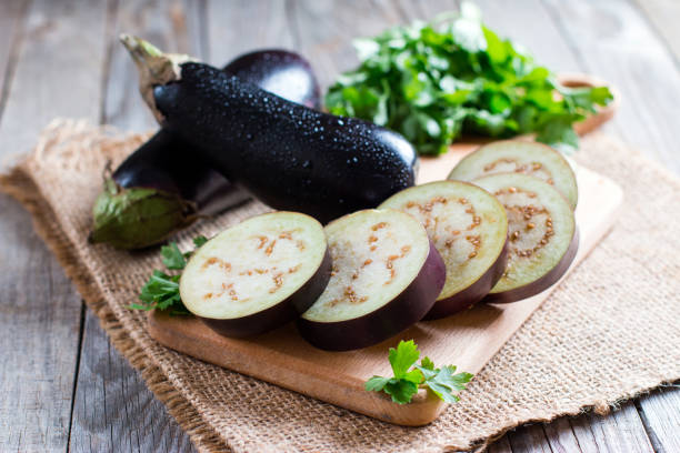 Sliced eggplant on wooden cutting board stock photo