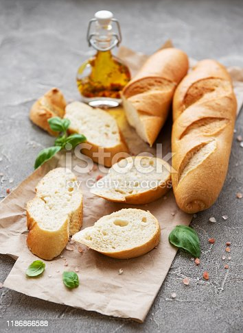 Sliced fresh crusty baguette with salt, olive oil  and basil on a grey concrete background