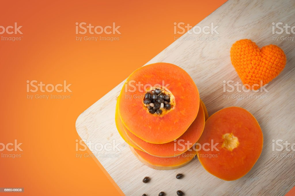 sliced fresh ripe papaya and papaya seed on cutting board and orange heart shape sign on orange color background- healthy eating and dieting food. zbiór zdjęć royalty-free