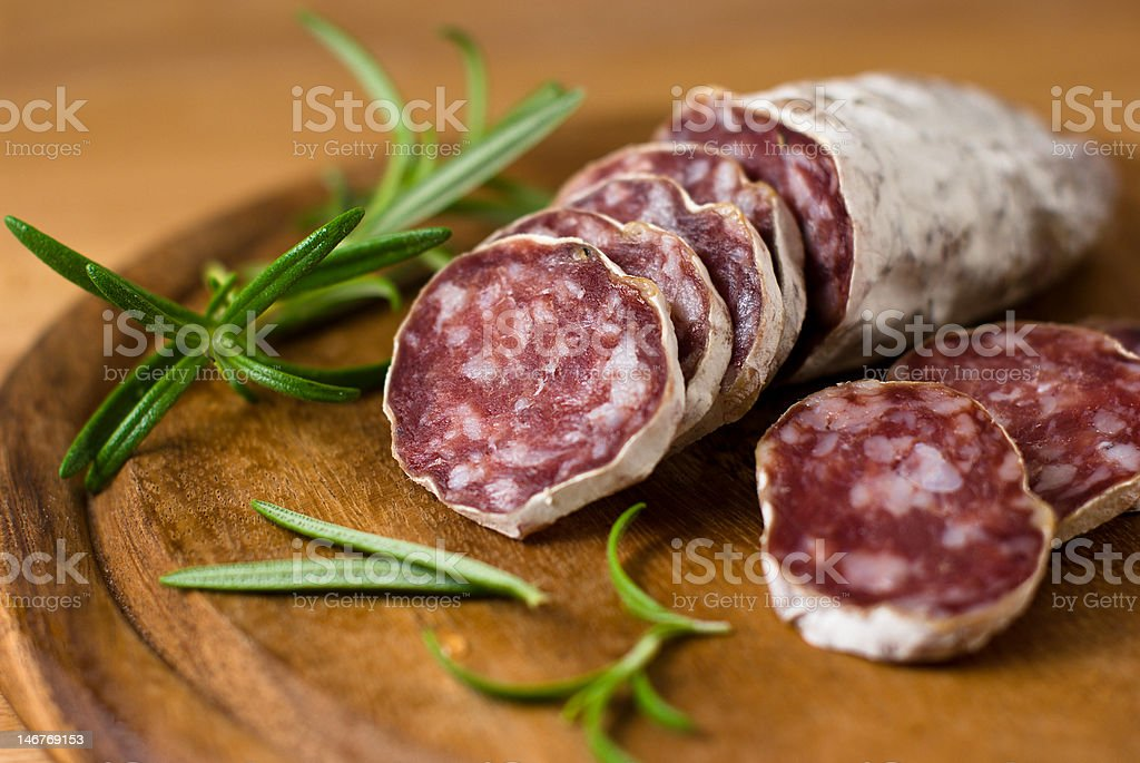 Sliced fresh salami on a wooden board stock photo