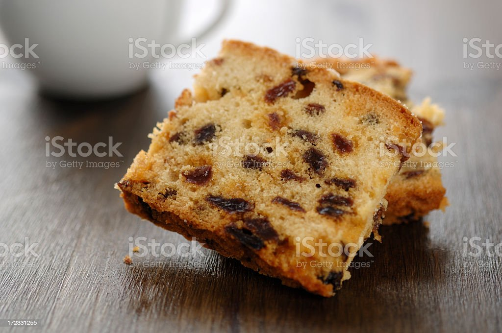 Sliced fruit cake with coffee cup in background stock photo