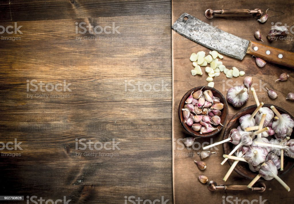 Sliced garlic cloves with an old knife. stock photo