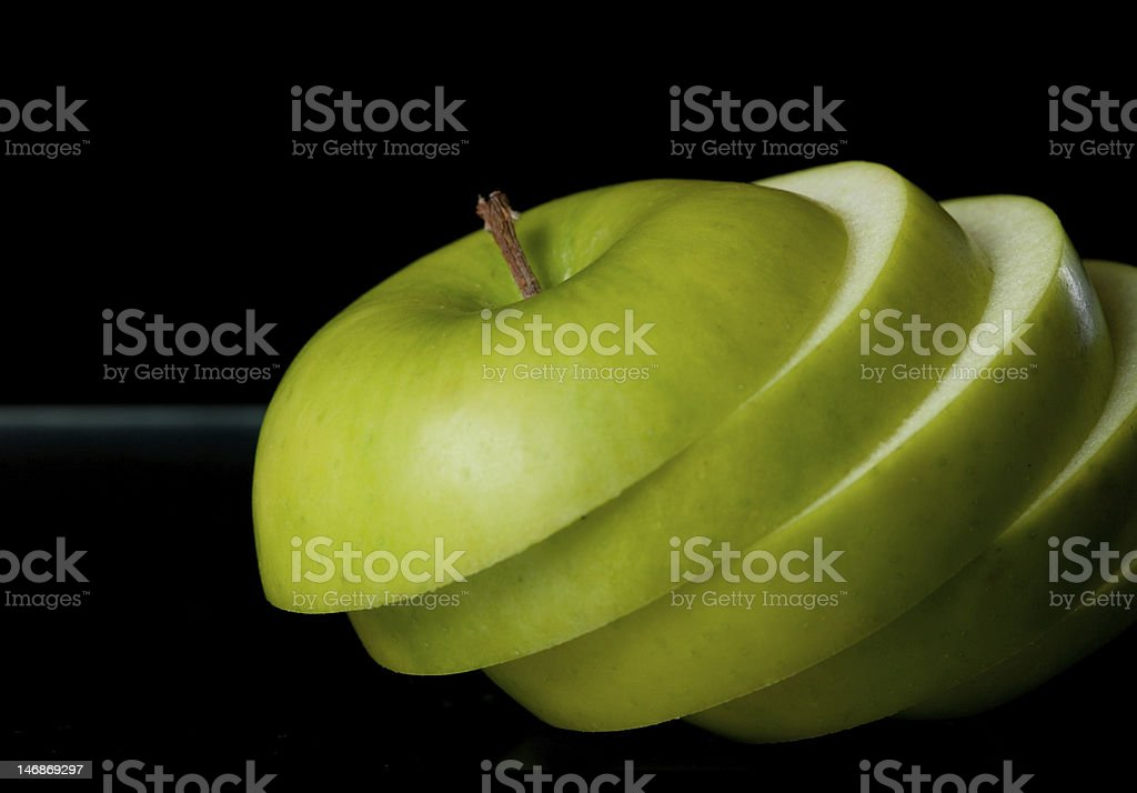 Sliced green apple close-up Sliced green apple on black background with horizon line. Apple - Fruit Stock Photo