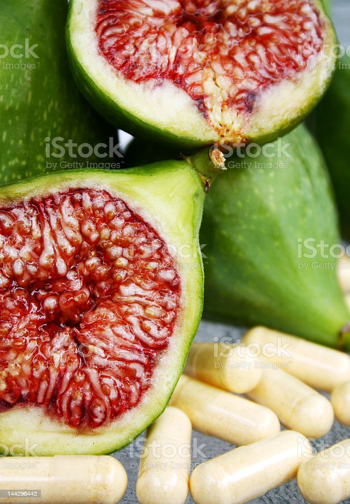 sliced green fig with vitamin supplements royalty-free stock photo