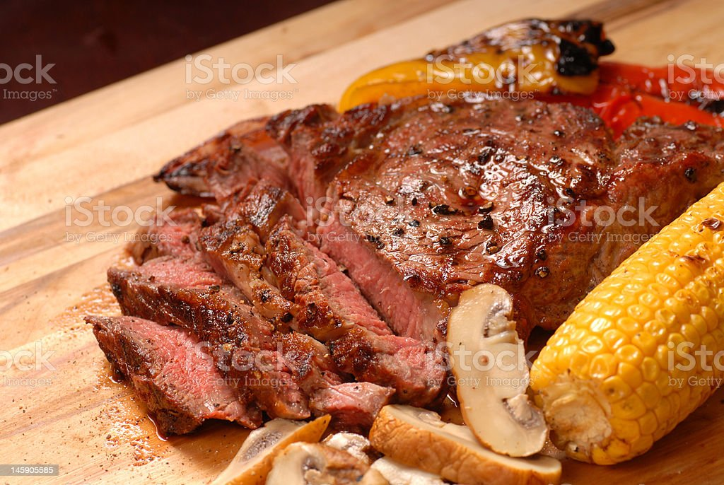 Sliced grilled BBQ ribeye steak with vegetables royalty-free stock photo