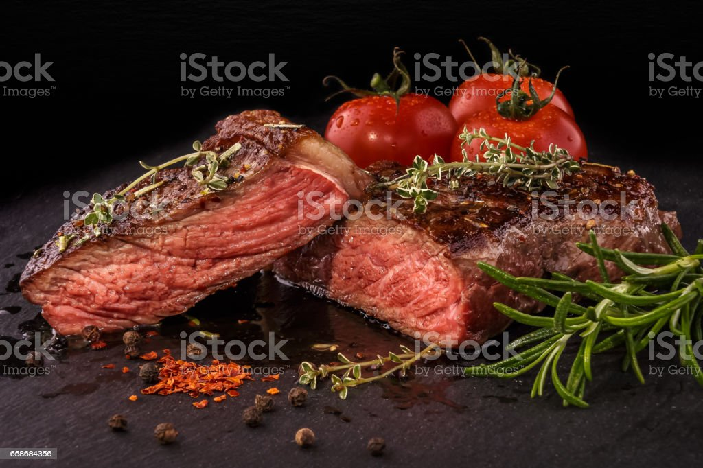 Sliced grilled beef steak with spices on slate slab stock photo
