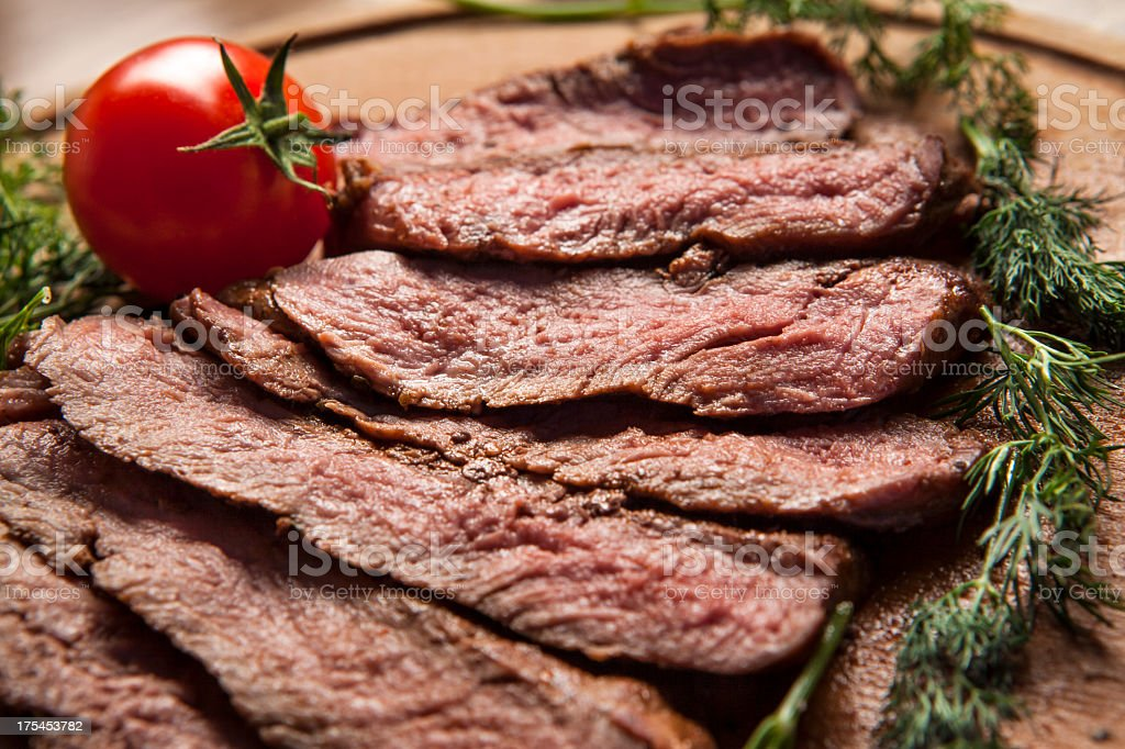 Sliced grilled meat displayed on wooden cutting board stock photo