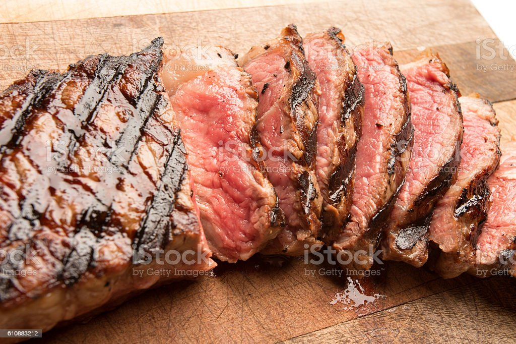 Sliced Grilled New York Steak on a Cutting Board stock photo