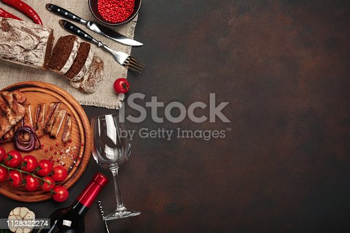 655794674istockphoto Sliced grilled pork steaks with bottle of wine, wine glass, corkscrew, knife, fork, black bread, cherry tomatoes, garlic, onion and rosemary on rusty background 1128322274