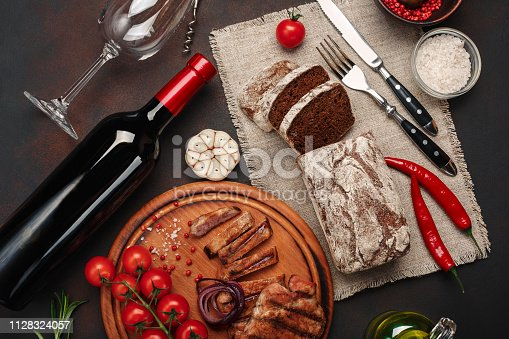655794674istockphoto Sliced grilled pork steaks with bottle of wine, wine glass, corkscrew, knife, fork, black bread, cherry tomatoes, garlic, onion and rosemary on rusty background 1128324057