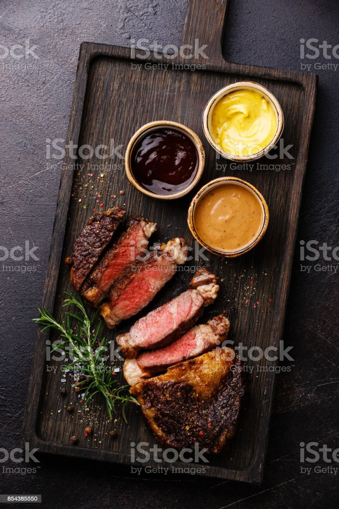 Sliced grilled Rib eye steak and three different sauces stock photo