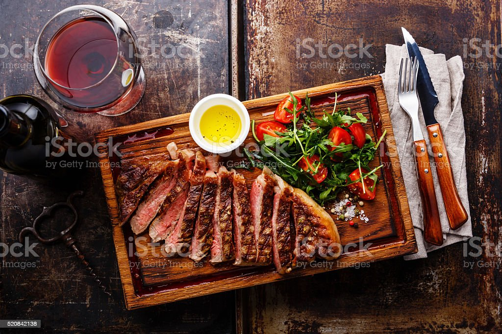 Sliced grilled steak and wine stock photo