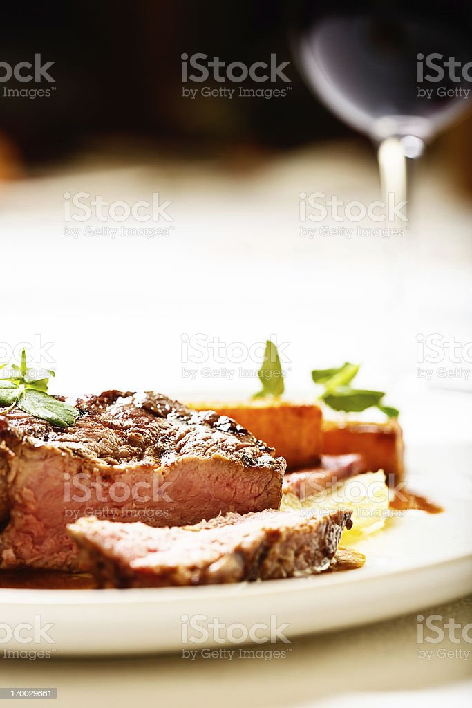 Sliced grilled steak with red wine in background: delicious! royalty-free stock photo
