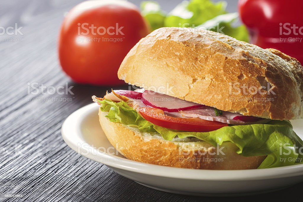 Sliced ham sandwich with tomatoes on a mixed seed bread stock photo