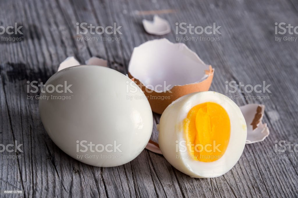 Sliced hard boiled eggs on wooden cutting board stock photo