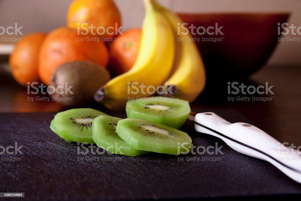 Fatias de frutas saudáveis, Faca de Cozinha no balcão. Kiwi, banana, laranja. foto royalty-free