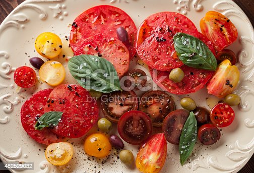 An overhead close up horizontal photograph of a variety of sliced heirloom tomatoes and olives garnished with fresh basil leaves, drizzled with chili oil and finished with flake salt and pepper.