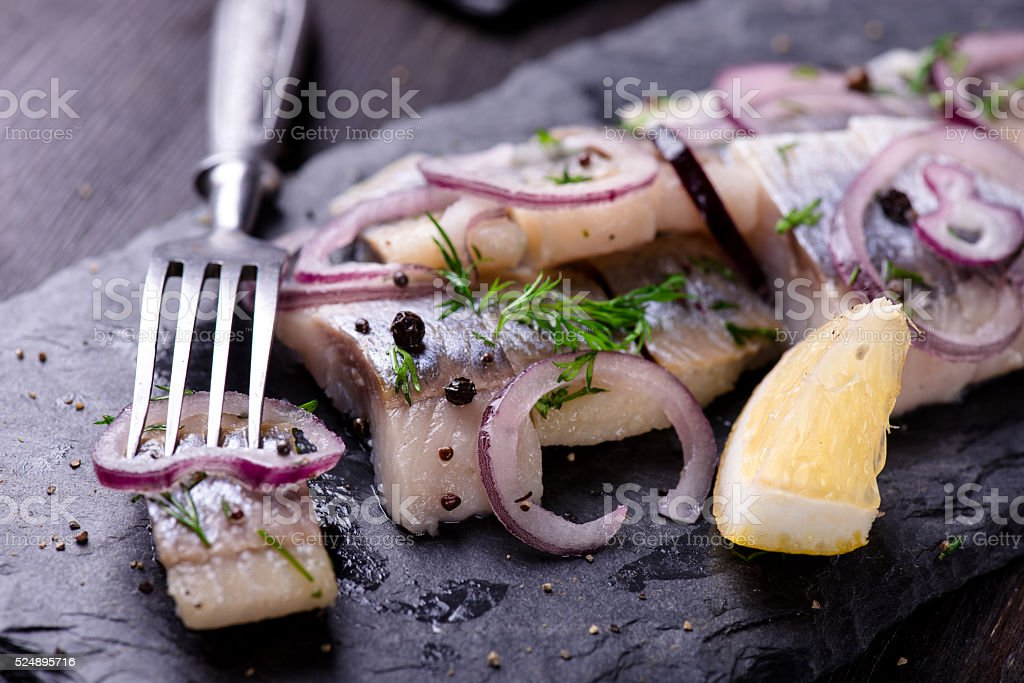 Sliced herring on a black slate plate royalty-free stock photo