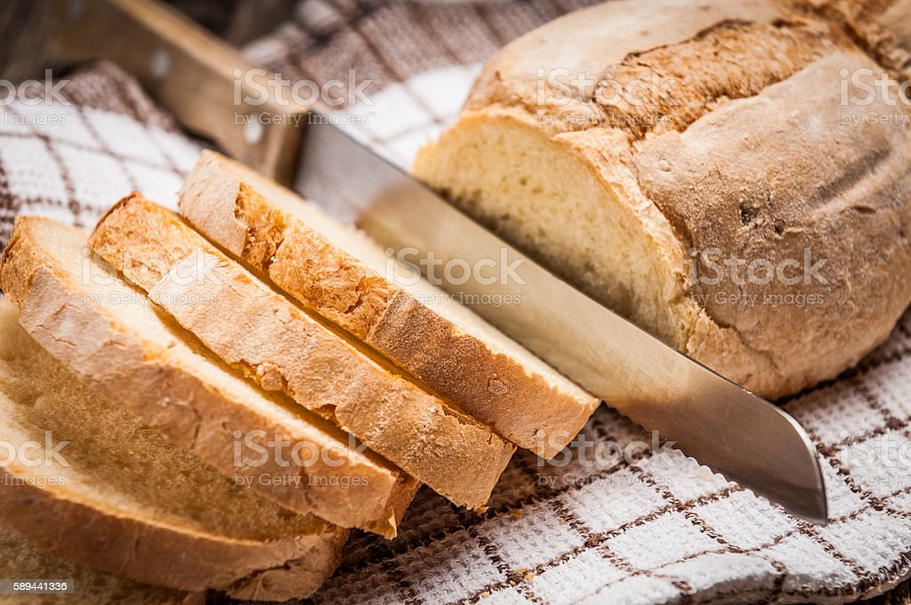 Sliced homemade bread on rustic wooden table stock photo