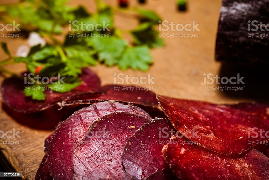 Sliced horse sausage, herbs and spices on cutting board. Selecti stock photo