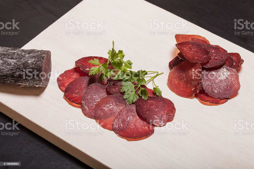 Sliced horse sausage, herbs and spices on cutting board. Toned stock photo
