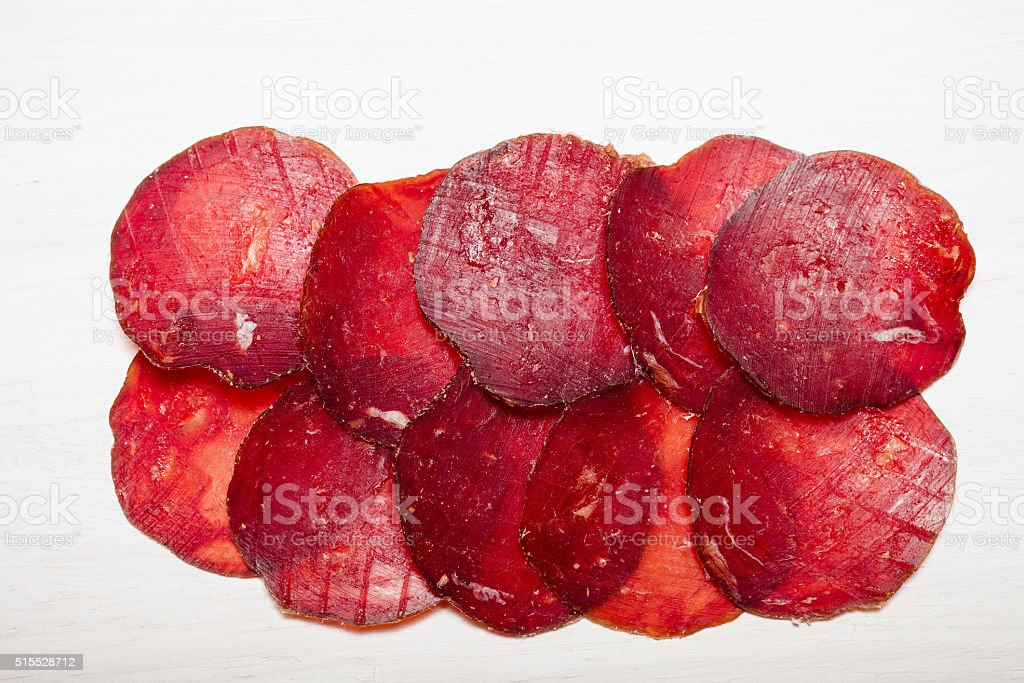 Sliced horse sausage on a white background. Toned stock photo