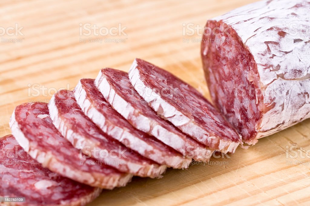 Sliced Italian sausage on a cutting board royalty-free stock photo
