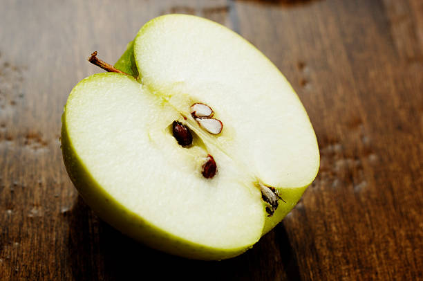sliced juicy crisp fresh green apple from above, against oak stock photo