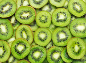 heap of sliced ripe kiwi as textured background