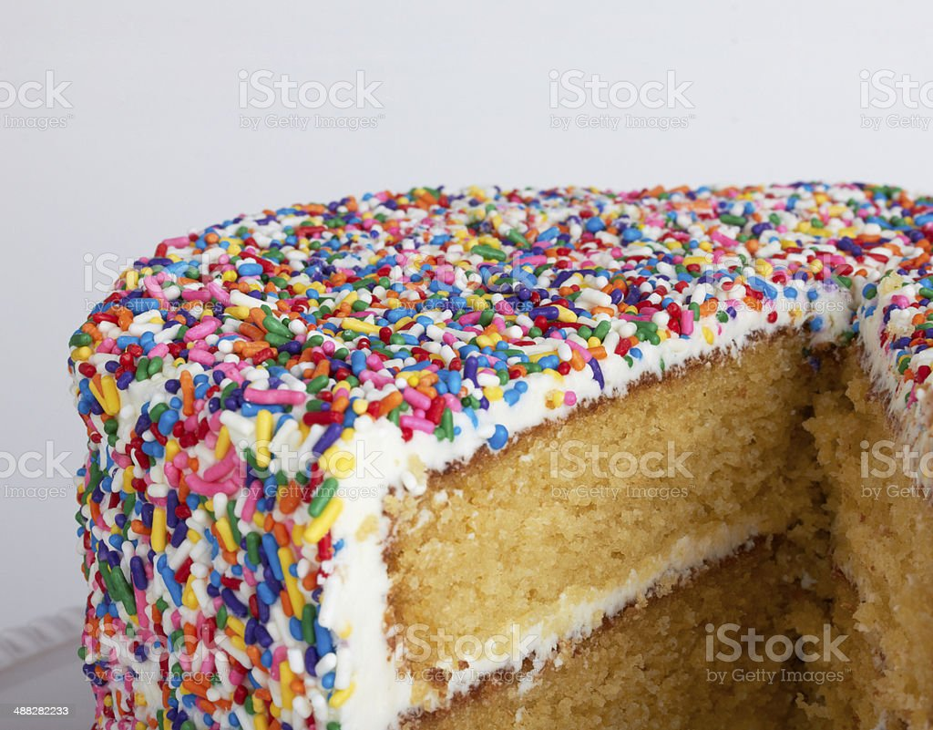 Sliced layer cake with sprinkles stock photo