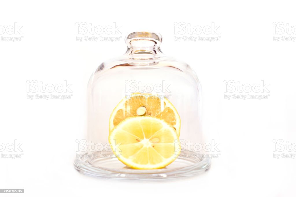 Sliced lemon on a saucer under a glass cap royalty-free stock photo