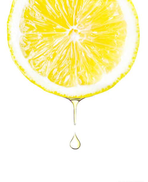 細く切ったレモンの絞り汁ドロップします。白で分離 - レモン ストックフォトと画像