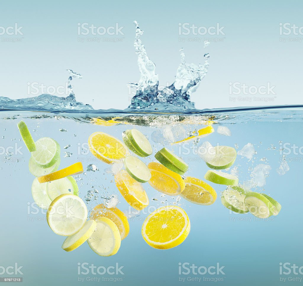 Sliced lemons and limes splashing in water royalty-free stock photo