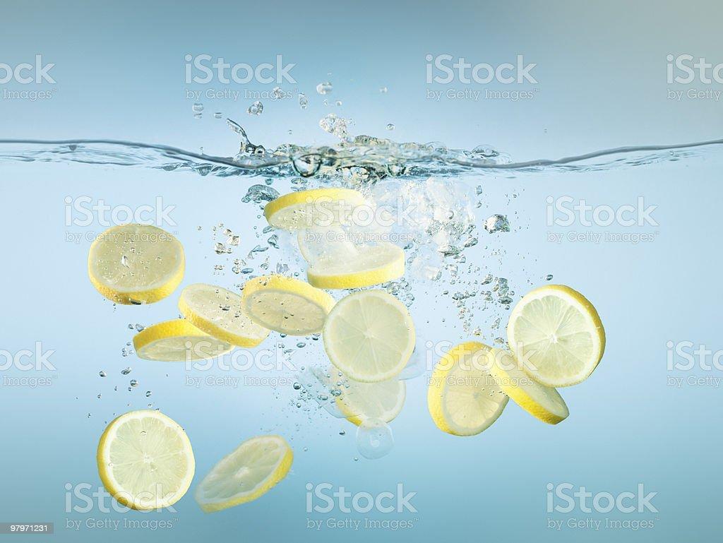Sliced lemons splashing in water royalty-free stock photo