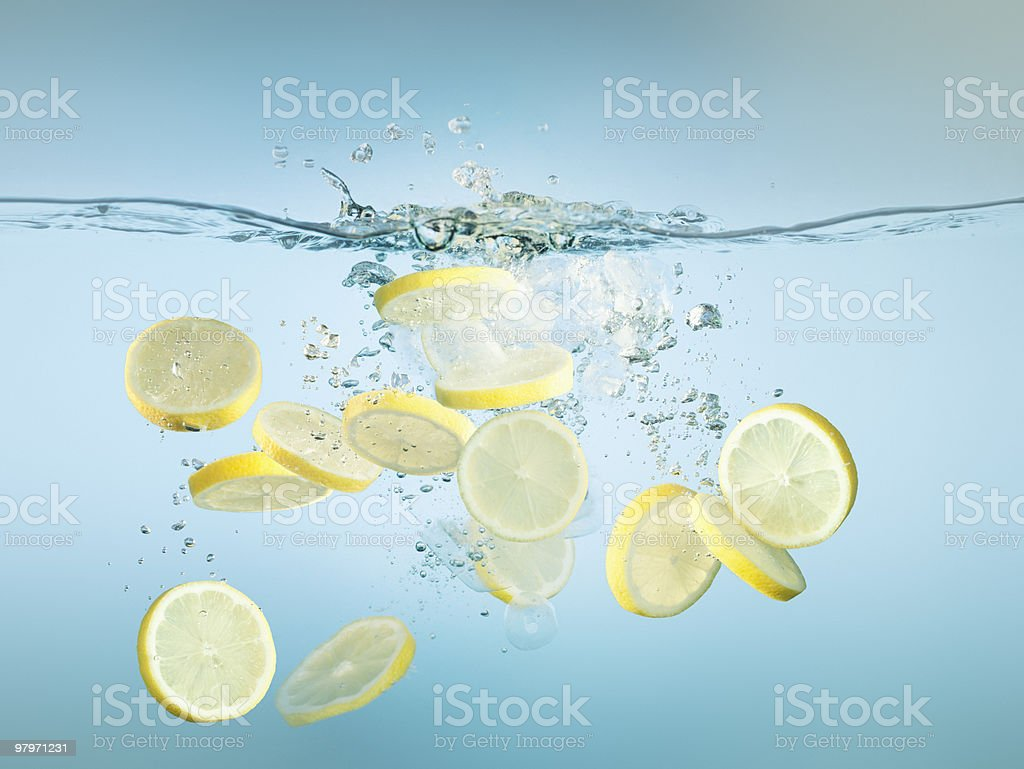 Sliced lemons splashing in water stock photo