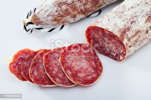 Sliced dry cured sausage Llonganissa from Catalonia on white background. Traditional Spanish meat products