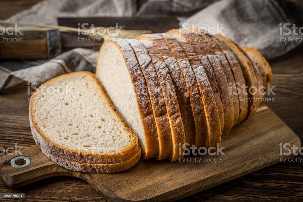 In Scheiben geschnitten Brot auf ein Schneidebrett. – Foto