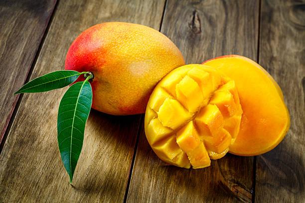 rodajas de mango en una mesa de madera. - mango fotografías e imágenes de stock