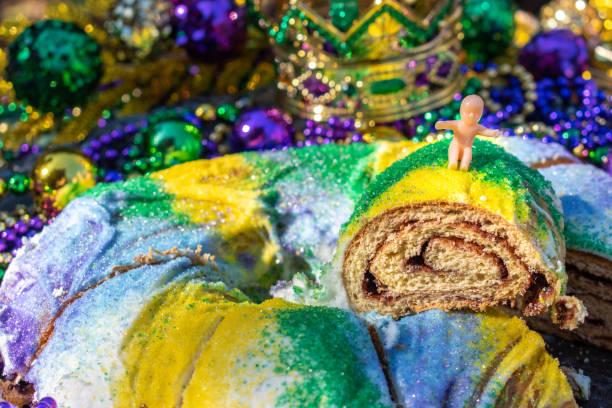 gâteau de roi de mardi gras tranché surmonté du bébé de jouet - galette des rois photos et images de collection