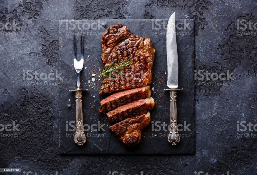 Sliced meat steak Striploin with knife and fork carving set stock photo