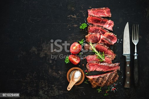 808351106istockphoto Sliced medium rare grilled beef ribeye steak 921029458
