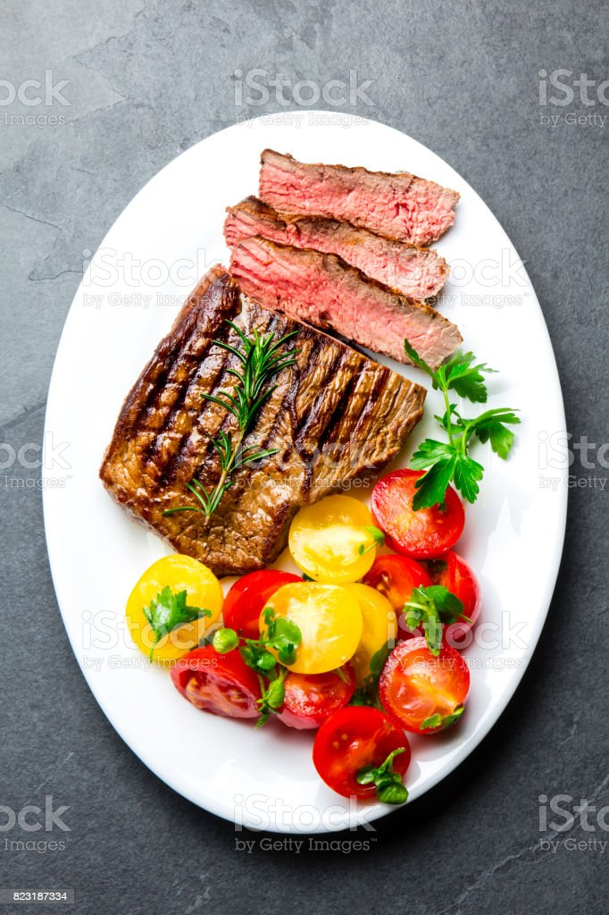 Sliced medium rare grilled beef steak served on white plate with tomato salad and potatoes balls. Barbecue, bbq meat beef tenderloin. Top view, slate background, copy space stock photo