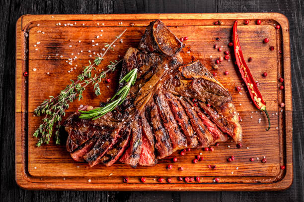 Sliced medium rare grilled steak on rustic cutting board with rosemary and spices , dark rustic wooden background, top view Sliced medium rare grilled steak on rustic cutting board with rosemary and spices , dark rustic wooden background, top view, place for text overhead projector stock pictures, royalty-free photos & images