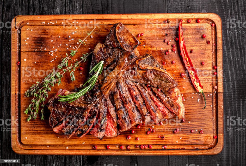 Sliced medium rare grilled steak on rustic cutting board with rosemary and spices , dark rustic wooden background, top view royalty-free stock photo