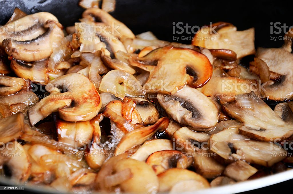 sliced mushrooms stir-fried in a pan. close-up full frame stock photo