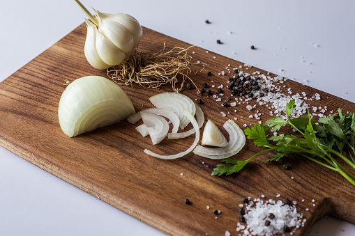 Sliced onion and spring garlic with sea salt and black pepper on a rustic wooden cutting board