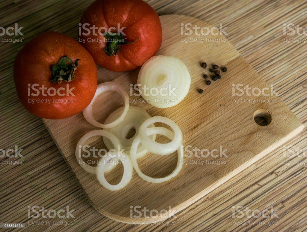 Oignon émincé, les tomates entières et poivre noir sur une planche à découper chêne photo libre de droits